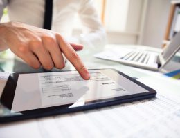 Businessperson Analyzing Invoice On Digital Tablet