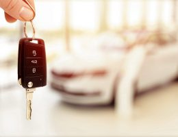 car sales showroom and person holding car key in hands