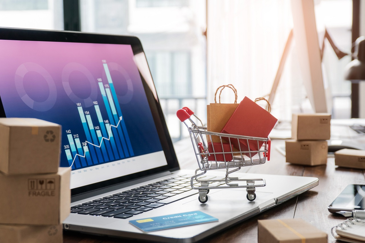 Shopping bags in shopping cart and credit card on laptop with paper boxes on table and sales data economic growth graph on screen, buying and selling services online on network, online shopping and e-commerce concept